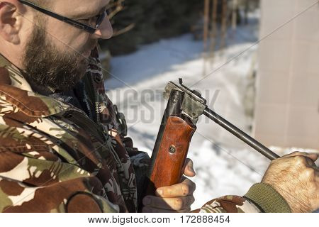 Man in winter forest reloads pneumatic weapons.  Hunter dressed in camouflage with pneumatic gun, rifle  The man in the white winter forest loads long arms.