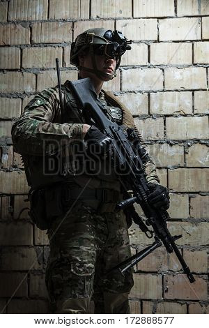 US Army Ranger with machinegun and night vision goggles standing near the wall. Side view profile