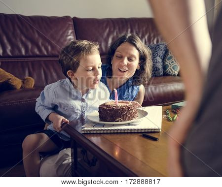 Family celebrate birthday party with chocolate cake