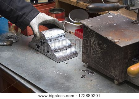 Melted alloy bars stacked in a pyramid on a workbench. Craftsman plant produces components for the machines.