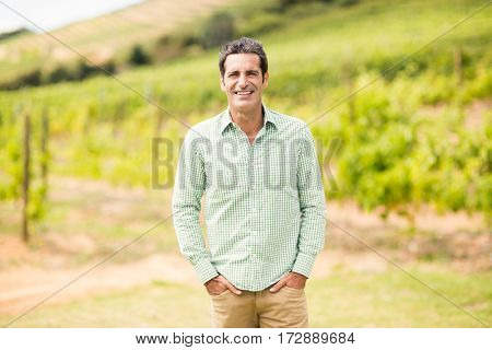 Portrait of vintner standing with hands in pockets in vineyard
