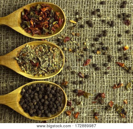 seasonings on a wooden spoon on sacking top view