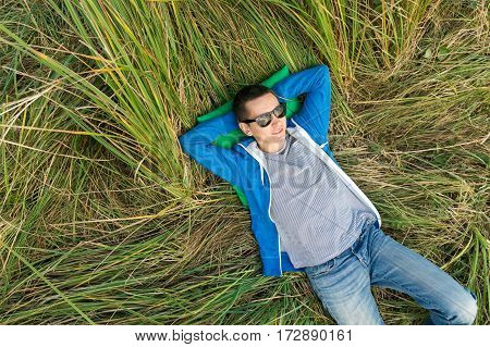 the happy young man has a rest outdoors. break from work in the fresh air. the smiling man lies on a green grass in the summer