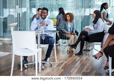 Smiling businessman talking on mobile phone while having coffee in office