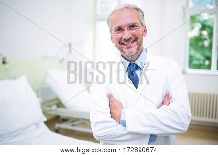 Portrait of smiling doctor standing with arms crossed in hospital