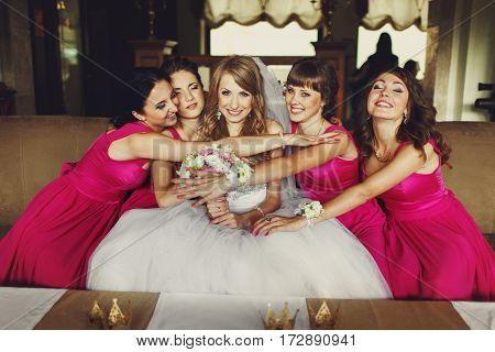 Bridesmaids In Pink Dresses Hug A Bride Sitting On The Sofa
