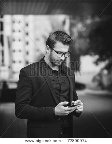 Young businessman in suit using mobile phone and reading email