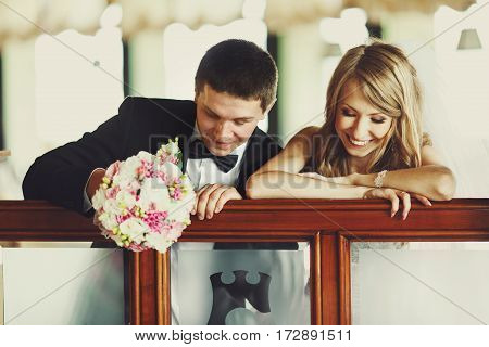 A Wedding Couple Looks Down Leaning On A Handrail