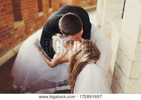 Groom Bends Bride Over And Kisses Her Standing On The Balcony