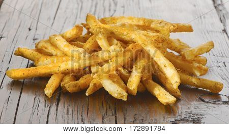 French fries over rustic wood with creole seasoning