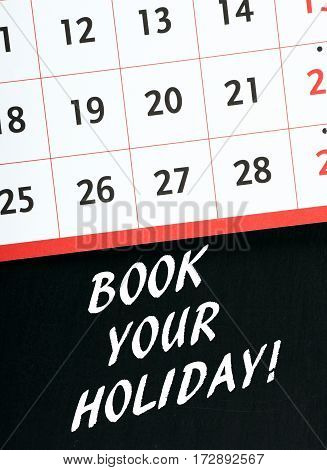 The words Book Your Holiday in white text on a blackboard beneath a calendar page as a reminder to schedule vacation time