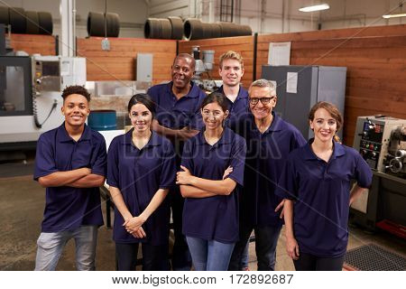 Portrait Of Engineers And Apprentices In Busy Factory