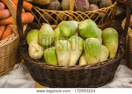 Green turnip in basket at agricultural market, close up