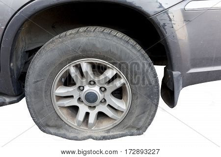 close up of a flat tire of a rusty old car centered on gravel road.