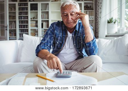 Tensed senior man checking the bills at home