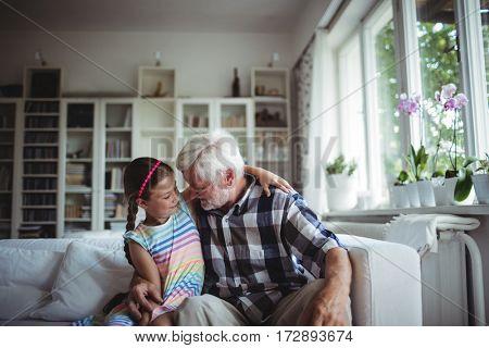 Senior man embracing his granddaughter at home