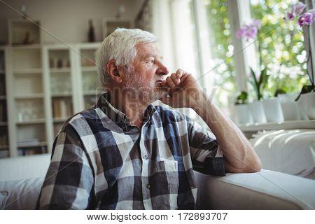 Thoughtful senior man sitting on sofa at home