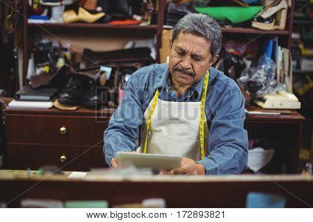 Shoemaker using digital tablet in workshop