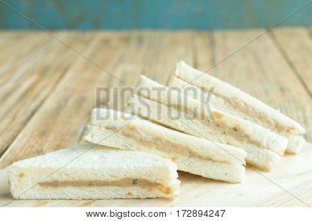 four tuna sandwiches on the wood background