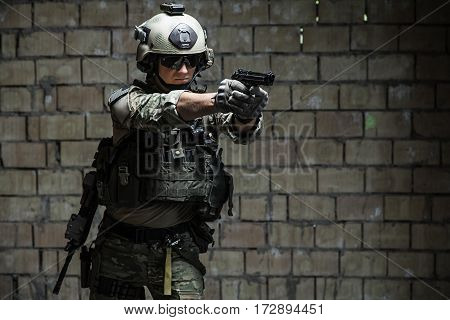 US Army Ranger aiming pistol with two hands. Shooting stance and grip