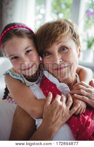 Portrait of granddaughter embracing her grandmother at home