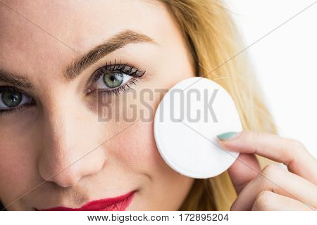 Close-up of beautiful woman posing with make-up sponge against white background
