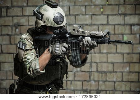 US Army Ranger aiming rifle with two hands. Shooting stance and grip