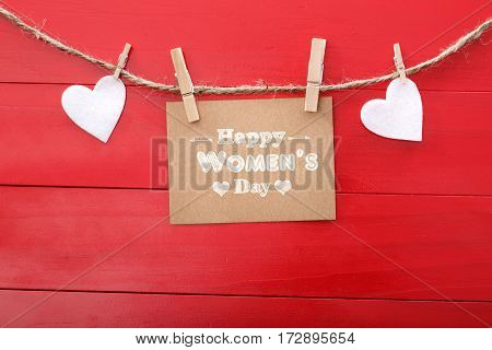 Womens day message with felt hearts hanging with clothespins over red wooden board