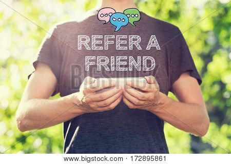 Refer A Friend concept with young man holding his smartphone outside in the park toward sunset