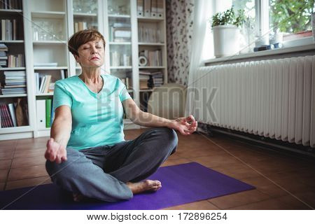 Senior woman meditating in lotus position at home