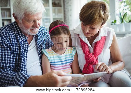 Grandparents and grand daughter looking at photo album in living room at home