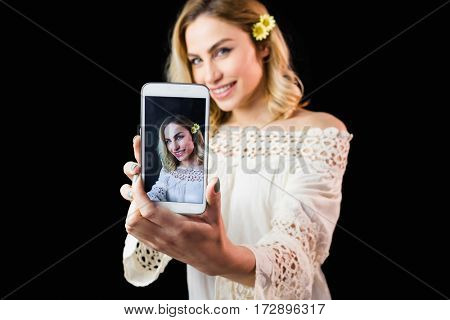 Portrait of beautiful woman clicking photo from mobile phone against black background