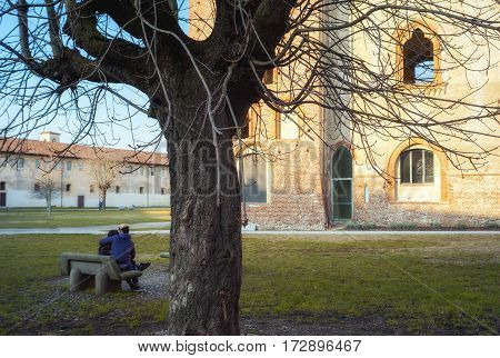 VIGEVANO, ITALY - FEBRUARY 14, 2017: a young couple of lovers, in the garden of the Ducale palace in Vigevano (Lombardy, Northern Italy), during San Valentine day (lovers holiday). Color image.