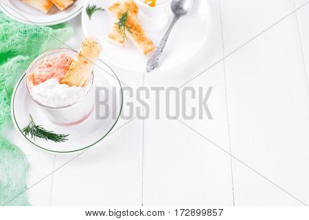 bowl of cream cheese with crispy toasts, dip sauce on wooden white background, copy space