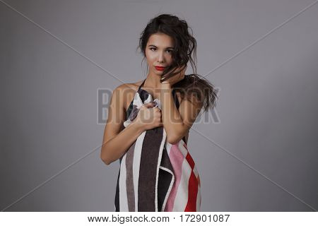 Fashion photo of beautiful and young lady in swimsuits posing in studio, holding colorful towel