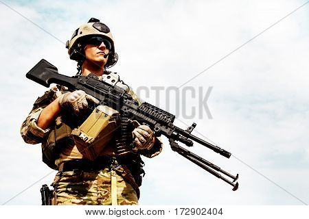 Low angle portrait of US Army Ranger with machinegun on blue sky background looking up. National pride concept