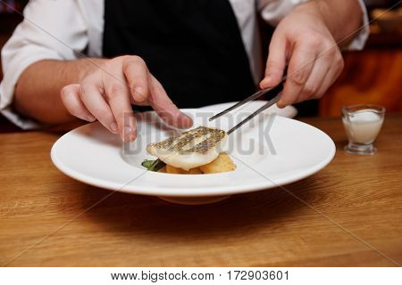 Chef is making appetizer with fish fillet using pincers