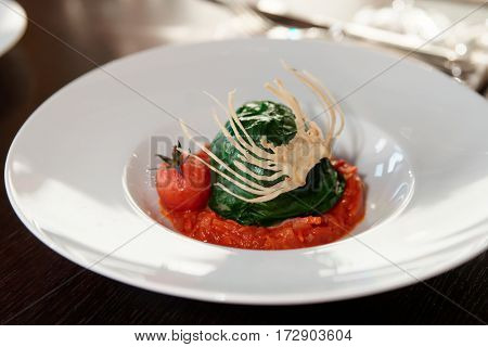 Stuffed spinach leaves with tomato sauce and cabbage chips, close-up