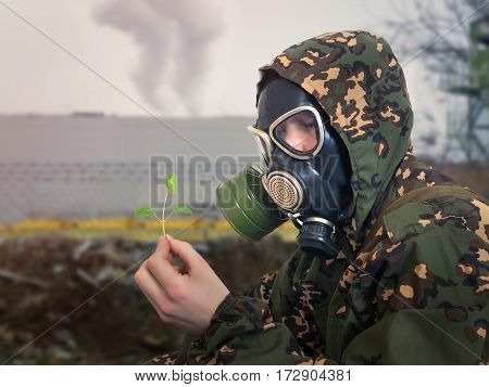 Soldier in gas mask looks on a small green plant. People in the form of camouflage.