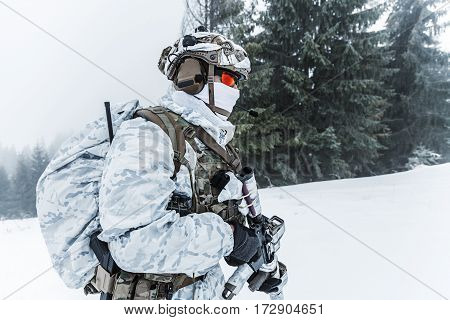 Winter arctic mountains warfare. Action in cold conditions. Trooper with weapons in forest somewhere above the Arctic Circle. Profile, side view