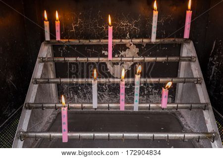 KAMAKURA, JAPAN - NOVEMBER 10, 2016: Candles burn in a place of worship of Hase-dera temple in Kamakura, Japan. Hase-dera Buddhist temple is famous for housing a massive wooden statue of Kannon.