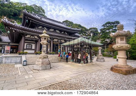 KAMAKURA, JAPAN - NOVEMBER 10, 2016: Tourists at the Hase-dera temple in Kamakura, Japan. Hase-dera Buddhist temple is famous for housing a massive wooden statue of Kannon.