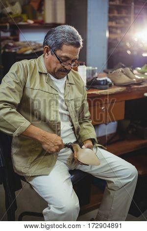 Shoemaker repairing a high heel in workshop