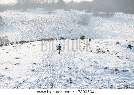 Hills with a hiker covered in snow.