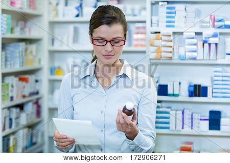 Pharmacist looking at prescription and medicine container in pharmacy