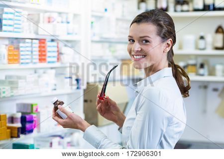 Portrait of pharmacist holding a medicine bottle in pharmacy