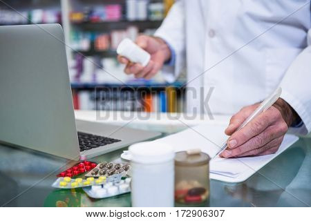 Pharmacist writing prescriptions for medicines in pharmacy