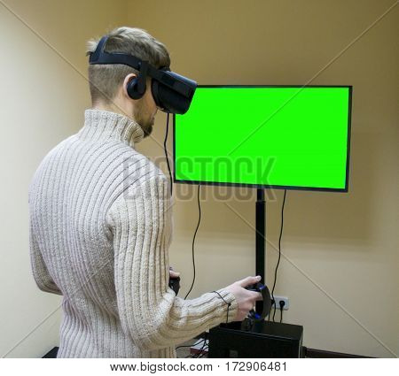 Man in helmet virtual reality plays game. Green screen. VR-headset display with headphones for virtual reality game in office. High-tech devices. Augmented reality device creating virtual space