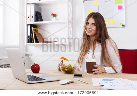 Woman has healthy business lunch in modern office interior. Young beautiful businesswoman at working place, eating vegetable salad in bowl, diet and vegetarian nutrition concept.