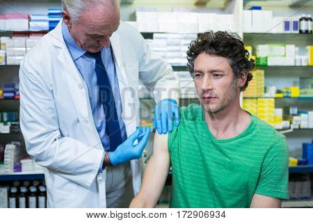 Pharmacist giving injection to patient in pharmacy